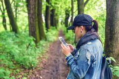 有智能手机的女孩在森林里 库存图片