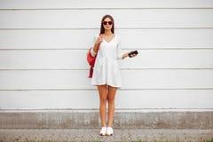有智能手机的女孩在街道上 免版税库存照片