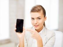 有智能手机的女实业家在办公室 免版税图库摄影