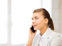 有智能手机的女实业家在办公室 免版税库存图片