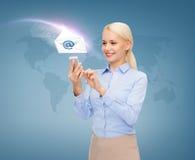 有智能手机的女实业家在蓝色背景 免版税库存照片
