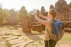 有智能手机的女性游人在吴哥城,柬埔寨 库存图片
