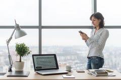 有智能手机的妇女在她的工作场所的办公室 库存照片