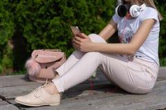 有智能手机的妇女在腿和耳机在脖子上坐一条长凳在公园和放松 免版税库存图片