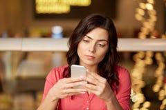 有智能手机的妇女在餐馆 库存图片