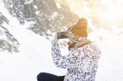 有智能手机的妇女在moutains和拍照片 自然光和太阳光 Moutains和自然本底 技术我 免版税库存图片