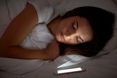 有智能手机的妇女睡觉在床上的在晚上 免版税库存图片