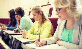 有智能手机的学生女孩在演讲 免版税库存照片