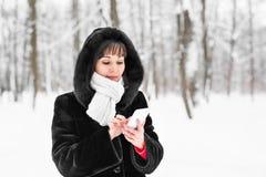有智能手机的少妇和冬天使在背景的雪花环境美化 免版税库存照片