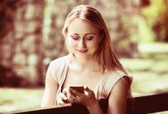 有智能手机的少妇在庭院里 免版税图库摄影