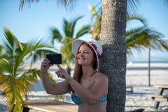 有智能手机的年轻女人在棕榈前面 免版税库存照片