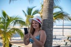 有智能手机的年轻女人在棕榈前面 库存图片