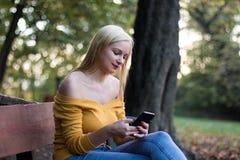 有智能手机的年轻白肤金发的妇女坐一个长木凳在公园,享受自然 免版税库存照片
