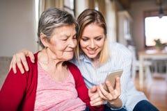 有智能手机的年长祖母和成人孙女在家 免版税库存图片