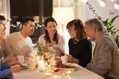 有智能手机的幸福家庭在茶会在家 库存图片