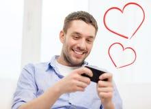 有智能手机的微笑的人在家 库存图片