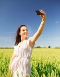 有智能手机的微笑的女孩在麦田 免版税库存图片