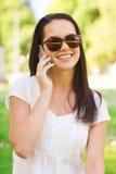 有智能手机的微笑的女孩户外 库存照片