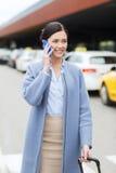 有智能手机的微笑的妇女在出租汽车在城市 库存照片