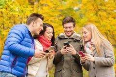 有智能手机的微笑的朋友在城市公园 图库摄影