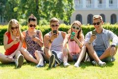 有智能手机的微笑的朋友坐草 免版税库存图片