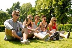 有智能手机的微笑的朋友坐草 库存图片