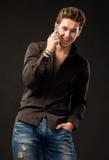 有智能手机的微笑的英俊的人 免版税库存照片
