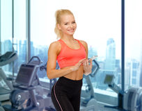 有智能手机的微笑的运动的妇女在健身房 免版税库存照片