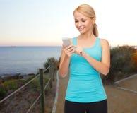 有智能手机的微笑的运动的妇女户外 免版税库存图片