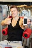 有智能手机的微笑的年轻人在健身房 免版税库存图片