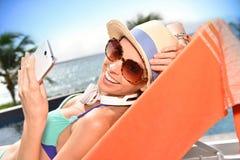 有智能手机的快乐的少妇在一把长的椅子 库存图片