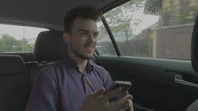 有智能手机的快乐的年轻人听在手机应用程序的一首歌曲和跳舞在他的旅行期间的由车 股票录像