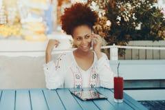 有智能手机的性感的黑人夫人在室外的咖啡馆 免版税库存照片