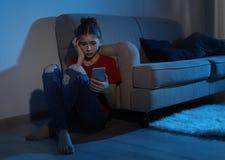 有智能手机的情感十几岁的女孩 互联网的危险 库存图片