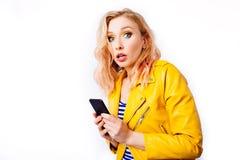 有智能手机的惊奇的白肤金发的女孩 免版税库存照片