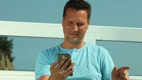 有智能手机的愉快的人由海 免版税库存照片
