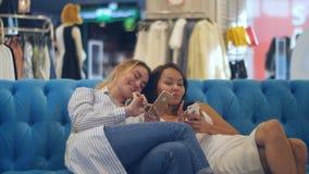 有智能手机的愉快的少妇和购物袋谈话在购物中心 库存图片