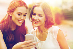 有智能手机的愉快的少妇在室外咖啡馆 免版税库存照片
