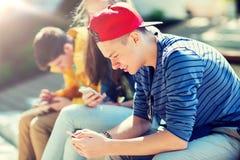 有智能手机的愉快的少年朋友户外 免版税库存图片