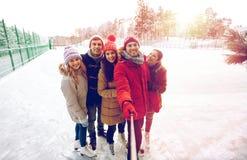 有智能手机的愉快的朋友在滑冰的溜冰场 库存照片