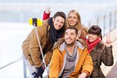 有智能手机的愉快的朋友在滑冰场 库存图片