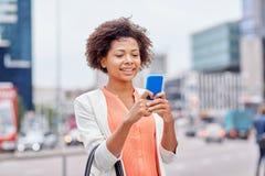 有智能手机的愉快的非洲女实业家 免版税图库摄影