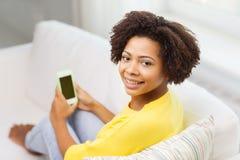 有智能手机的愉快的非洲妇女在家 免版税库存照片