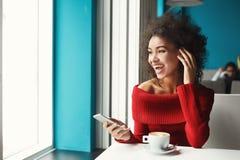 有智能手机的愉快的黑人女孩在咖啡馆 库存图片