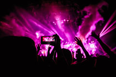 有智能手机的手记录实况音乐节日,拍音乐会阶段照片  免版税图库摄影