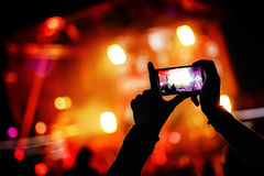 有智能手机的手记录实况音乐节日,生活音乐会,在阶段的展示 免版税库存照片