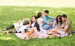 有智能手机的朋友在野餐在夏天停放 免版税图库摄影