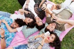 有智能手机的朋友在野餐毯子 库存照片