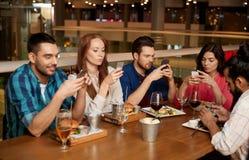 有智能手机的朋友在餐馆 免版税图库摄影