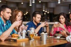 有智能手机的朋友用餐在餐馆的 免版税库存照片